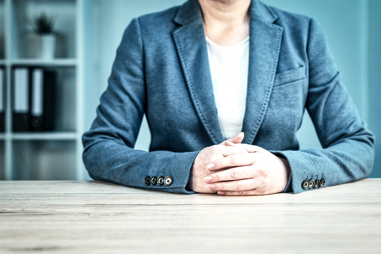 Businesswoman with arms clasped on table